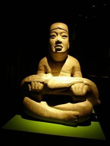 Greenstone figure of a youth holding a limp were-jaguar baby, found in the Mexican state of Veracruz in the Olmec heartland, is East Asian looking to most people